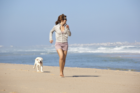 Happy young lady having fun with her dog at the beach